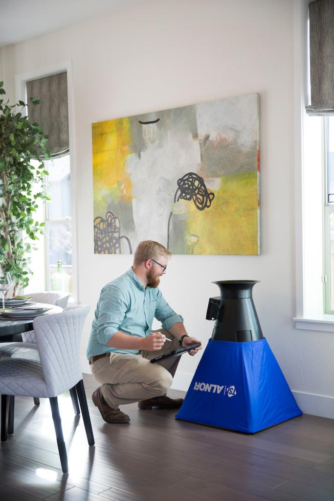 Thrive Home Builders Nathan Kahre measures a vent hood for flow and indoor air quality