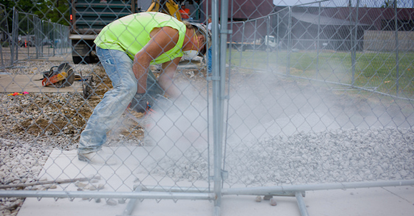 Construction worker cuts concrete kicking up a lot of silica dust.