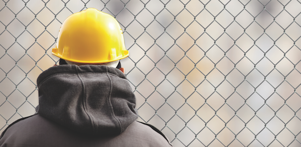 construction labor shortage-man in hardhat by chainlink fence-photo