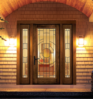 Therma-Tru's Zaha decorative glass featured in an entryway door lit at night.