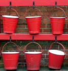 Photo showing rows of red buckets.