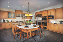 The warm wood cabinets and slate-gray flooring in this kitchen at Truewind, in Huntington Beach, Calif., by TRI Pointe Homes, is a recent example of the transitional look.