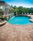 Panorama segmental pavers from Pavestone surround an organically shaped swimming pool.
